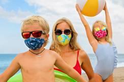Une famille profite de la plage en toute sécurité avec des masques