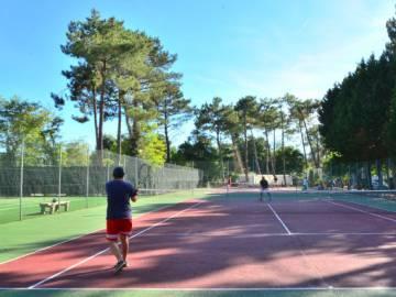 Vacanciers jouant un match de tennis sur l'un des 3 courts du camping Le Vieux Port dans les Landes