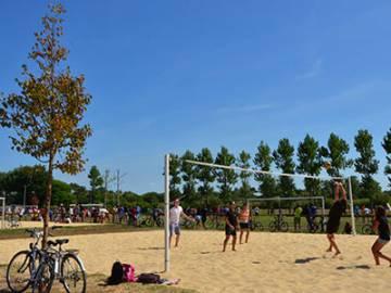 Vacanciers jouant au beach volley sur l'aire multisports du camping Le Vieux Port dans les Landes